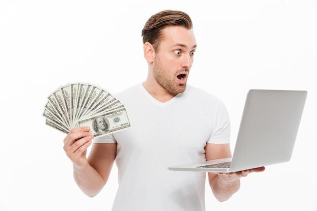Entsetzter junger mann, der geld unter verwendung der laptop-computers hält.