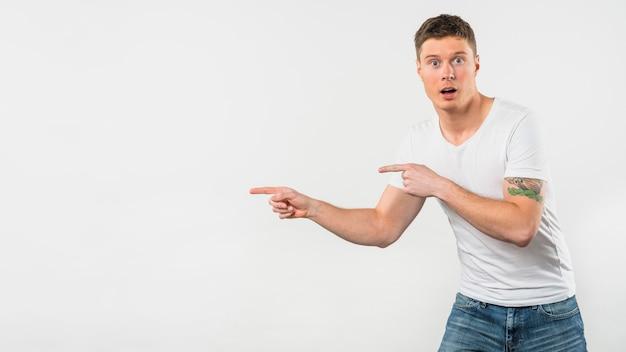 Entsetzter junger mann, der seine finger auf etwas lokalisiert auf weißem hintergrund zeigt