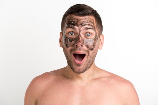 Entsetzter junger mann mit schwarzer maske auf gesicht über weißer wand
