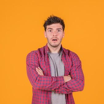 Entsetzter junger mann mit seinem arm kreuzte gegen einen orange hintergrund