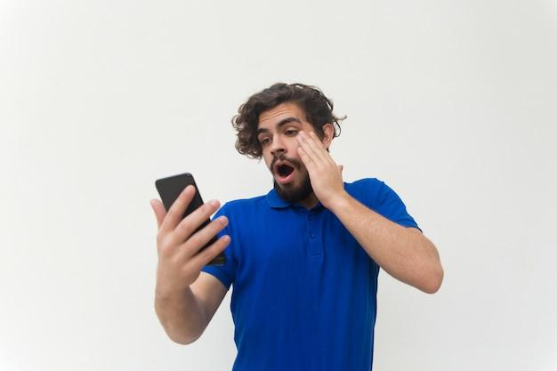 Entsetzter kerl mit der smartphonelesemitteilung, starrend entlang des schirmes an