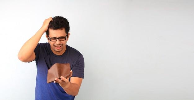 Entsetzter, überraschter sprachloser mann, der eine leere geldbörse auf weiß hält.