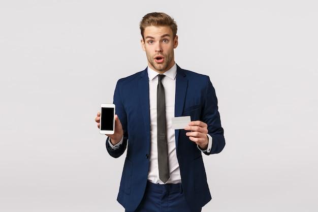 Entsetzter und beeindruckter hübscher geschäftsmann in der stilvollen klassischen blauen klage, kreditkarte und smartphone halten und zeigen bewegliche anzeige, sagen wow und starren erstaunt, fördern finanz-app