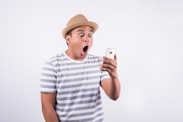 Entsetzter und überraschter asiatischer mann, der smartphone schaut
