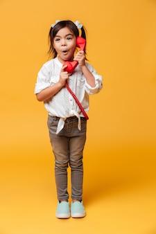 Entsetztes aufgeregtes kleines mädchen, das durch rotes retro- telefon spricht.