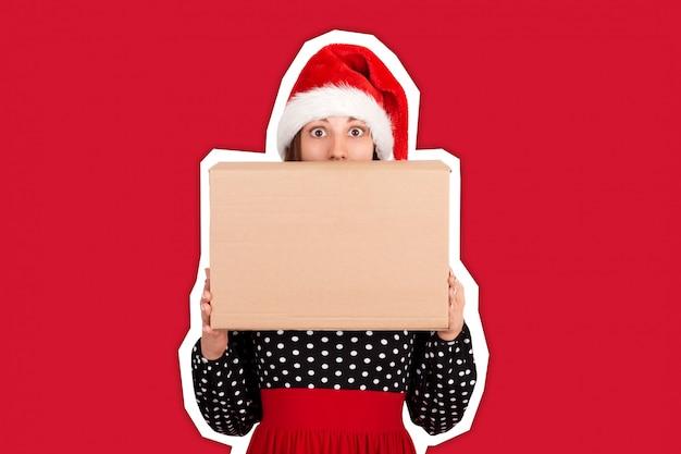 Entsetztes aufgeregtes mädchen, das großen geschenkkartonkasten steht und hält. copyspace. trendige farbe im stil einer zeitschriftencollage. ferien