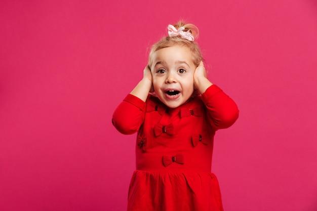 Entsetztes glückliches junges mädchen im roten kleid, das ihren kopf hält