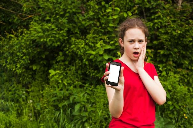 Entsetztes hübsches mädchen, das mobiltelefon des leeren bildschirms bei der stellung am park zeigt