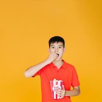 Entsetztes kind, das popcorn isst