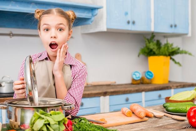 Entsetztes mädchen, das den deckel des kochens des topfes in der küche betrachtet kamera öffnet