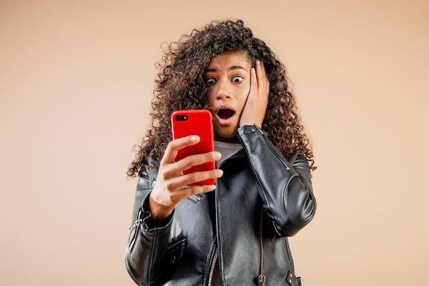 Entsetztes überraschtes schwarzes mädchen, das ihren telefonbildschirm lokalisiert über braun betrachtet