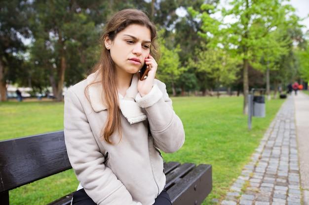 Entsetztes umgekipptes studentenmädchen, das am telefon spricht