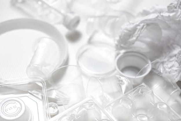 Entsorgung und entsorgung. ökologisches problem. leeres plastikgeschirr auf weißem hintergrund.