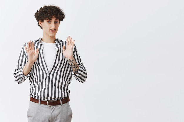 Entspann, sieh es gelassen. porträt eines freundlich aussehenden stilvollen männlichen freundes mit schnurrbart und lockiger frisur, die handfläche in der übergabe anhebt, um freund zu beruhigen, der versucht, problematische situation über grauer wand zu lösen