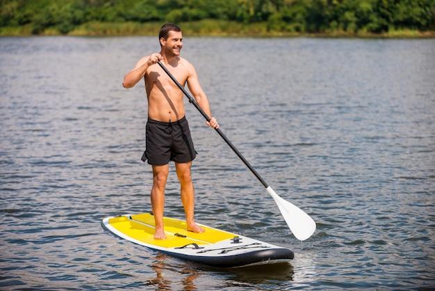 Entspannen auf dem paddleboard. hübscher junger mann, der auf seinem paddleboard surft und lächelt