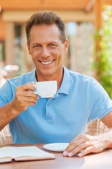 Entspannen bei einer tasse frischem kaffee. fröhlicher reifer mann, der kaffee trinkt und lächelt, während er draußen am tisch mit haus im hintergrund sitzt