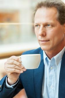 Entspannen bei einer tasse frischem kaffee. nachdenklicher reifer mann in abendkleidung, der kaffee trinkt und wegschaut, während er im café sitzt