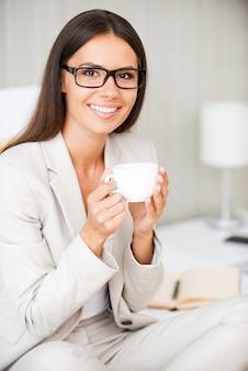 Entspannen bei einer tasse frischem kaffee. schöne junge lächelnde geschäftsfrau im anzug, die kaffee trinkt und lächelt, während sie auf dem bett im hotelzimmer sitzt