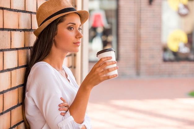 Entspannen bei einer tasse frischem kaffee. seitenansicht einer nachdenklichen jungen frau in einem funky hut, die eine tasse mit heißem getränk hält und wegschaut, während sie sich draußen an die wand lehnt