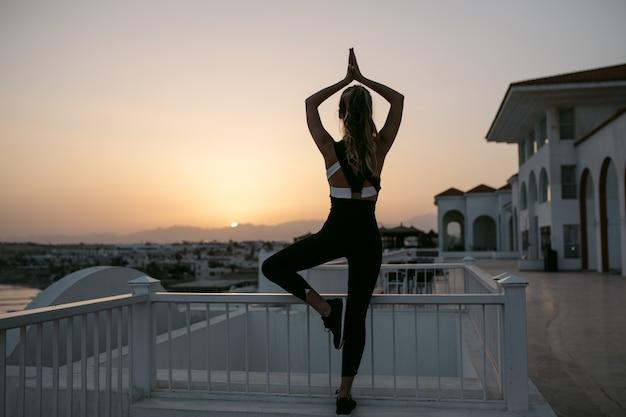 Entspannen beim yoga-training der hübschen sportlichen jungen frau von zurück, die zum sonnenaufgang am meer im tropischen land schaut. genießen sie training, gleichgewicht, fröhliche stimmung und einen gesunden lebensstil