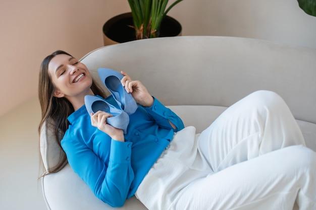 Entspannen. dunkelhaarige junge frau im blauen hemd, die auf einem sofa mit ihren schuhen in den händen liegt
