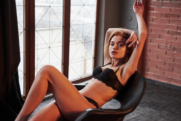 Entspannen. heißes wunderschönes junges mädchen in unterwäsche, das auf dem stuhl drinnen sitzt