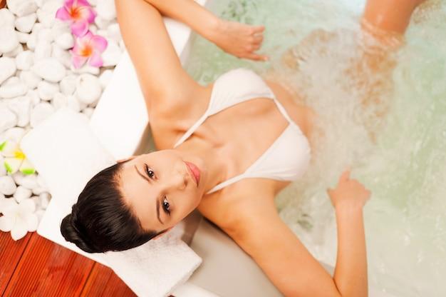 Entspannen im whirlpool. draufsicht einer attraktiven jungen frau, die sich im whirlpool entspannt und in die kamera schaut