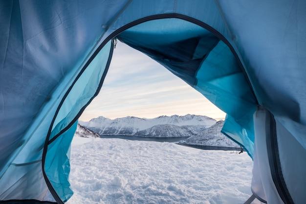 Entspannen in der kampierenden öffnung des zeltes mit schneebedecktem berg