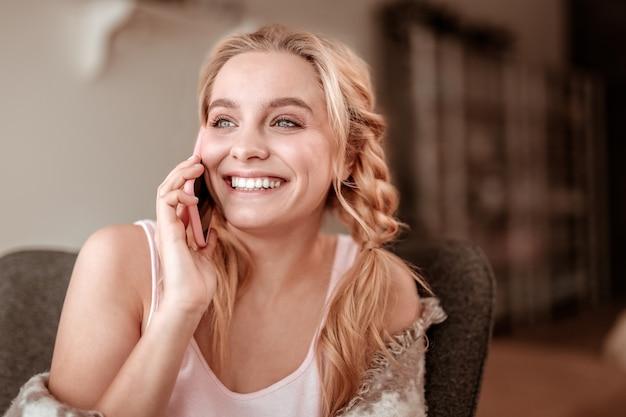 Entspannen in wohnungen. fröhliche blonde frau mit üppigen zöpfen, die während des gesprächs lachen und ihre weißen zähne zeigen