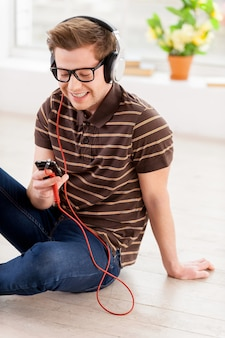 Entspannen mit musik. draufsicht auf einen gutaussehenden jungen mann, der seinen mp3-player anschaut und die musik hört, während er in seiner wohnung auf dem boden sitzt