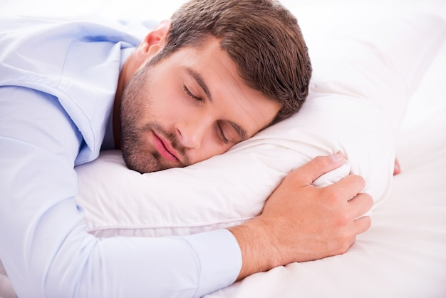 Entspannen nach einem harten arbeitstag. hübscher junger mann in hemd und krawatte, der im bett schläft