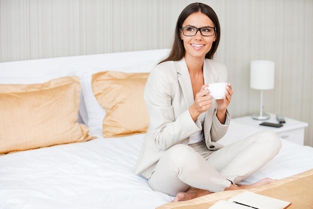 Entspannen nach einem harten arbeitstag. schöne junge lächelnde geschäftsfrau im anzug, die kaffee trinkt und wegschaut, während sie auf dem bett im hotelzimmer sitzt?