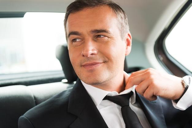 Entspannen nach geschäftsreise. zufriedener reifer geschäftsmann, der seine krawatte beim sitzen auf dem rücksitz eines autos anpasst