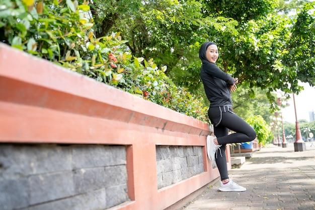 Entspannen sie die muslimische sportlerin, die ihren körper im freien im park ausübt