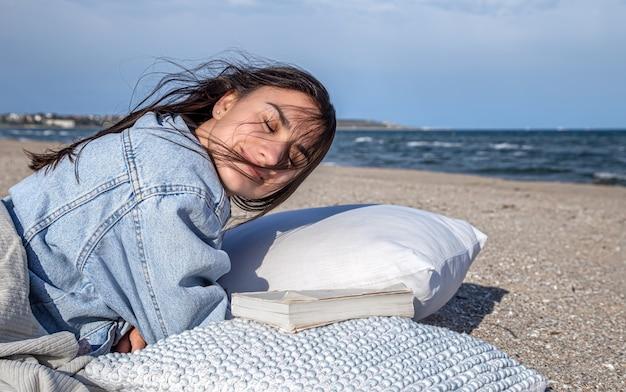 Entspannen sie konzept, eine frau am strand bei windigem wetter, die auf einem kissen mit einem buch ruht.