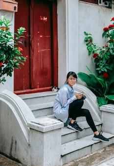Entspannen sie sich den asiatischen frauenreisenden, der auf treppenhaus mit der hand sitzt, die digitalkamera hält