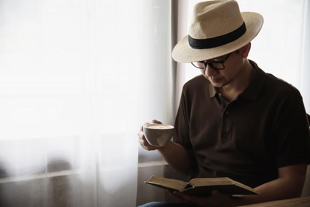 Entspannen sie sich den asiatischen mann, der einen kaffee trinkt und ein buch liest