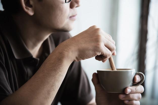 Entspannen sie sich den asiatischen mann, der einen kaffee trinkt