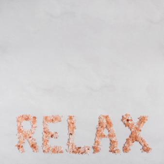 Entspannen sie sich den text, der mit himalajakräutersalz auf weißem hintergrund gemacht wird