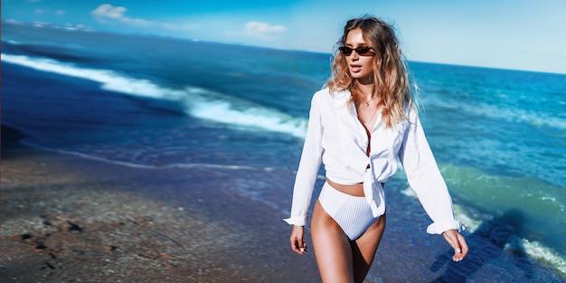 Entspannen sie sich die elegante frau, die sich am strand ausruht, schöne weiblichkeit, blondes haar, dame, ruhe und freiheitskonzept