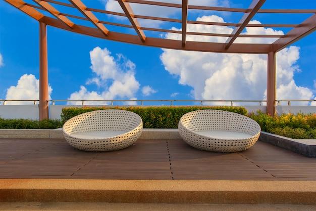 Entspannen sie sich ecke auf kondominiumdachspitzengarten mit stühlen auf hintergrund des blauen himmels