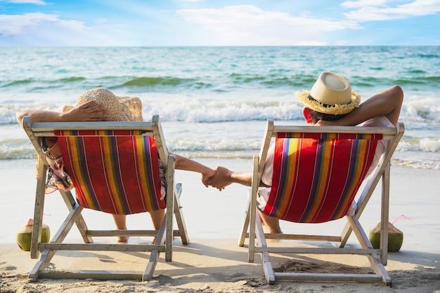 Entspannen sie sich paare, die auf strand chiar mit seewelle niederlegen - mann und frau haben ferien am seenaturkonzept