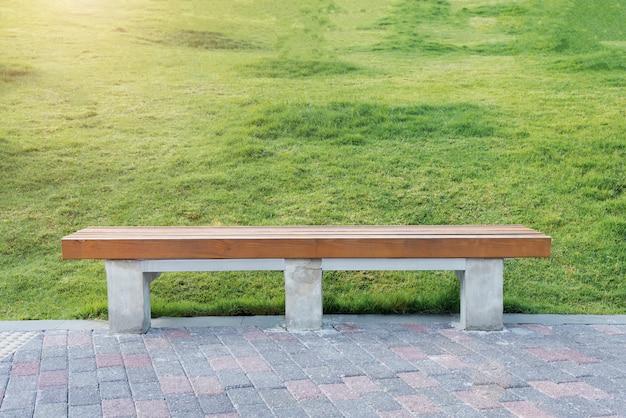 Entspannen sie sich und machen sie ein ruhekonzept. hölzernes chesterfield mit ziegelsteinboden und grünem gras im park