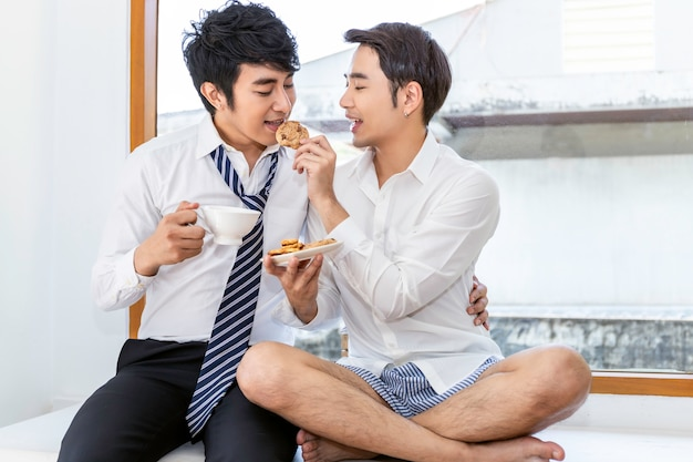 Entspannen sie sich und teezeit. porträt von den asiatischen homosexuellen paaren, die plätzchen essen und genießen lustigen moment