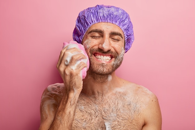 Entspannen, spa, hygiene, weichheit konzept. freudig lächelnder junger mann mit breitem lächeln, zeigt weiße perfekte zähne, reibt wange mit schwamm, hat schaum am körper