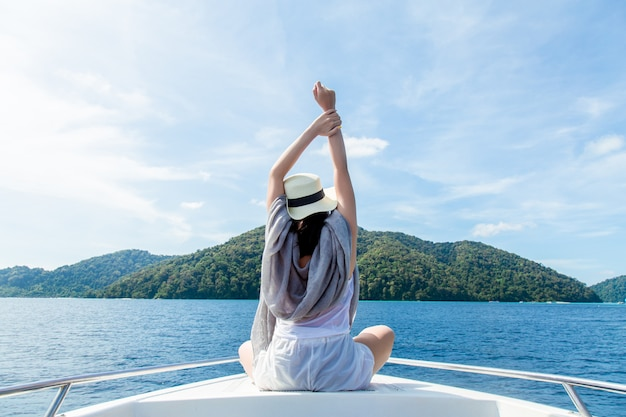 Entspannende ferien der jungen frau auf dem boot und das schauen des vollkommenen meeres
