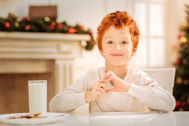 Entspannende ferien. nettes kleines oy, das an einem tisch sitzt und lächelt und selbstgebackene lebkuchenplätzchen mit einem glas milch isst.