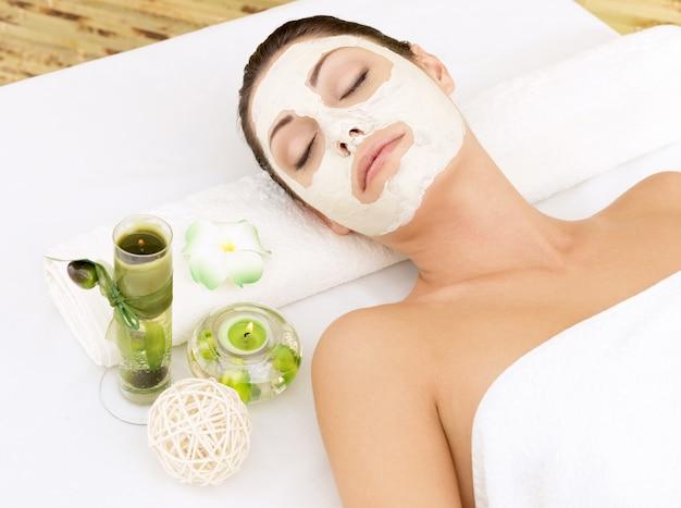 Entspannende frau am spa-salon mit kosmetischer maske auf gesicht.