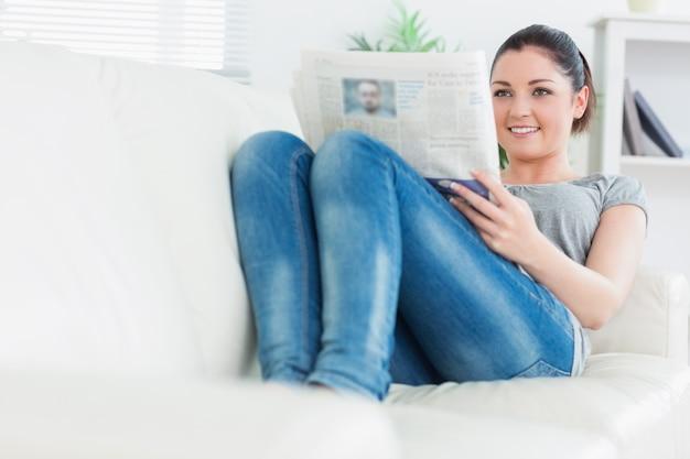 Entspannende frau, die auf der couch liegt und zeitung liest