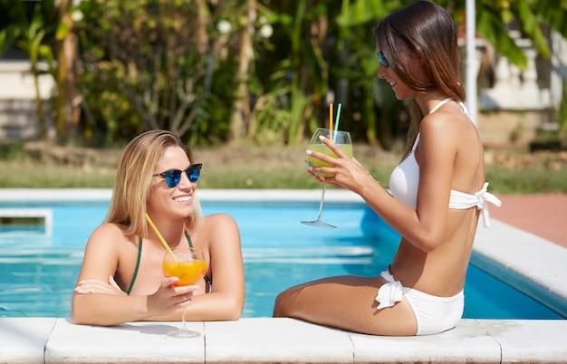 Entspannende frau und getränk ein cocktail am swimmingpool